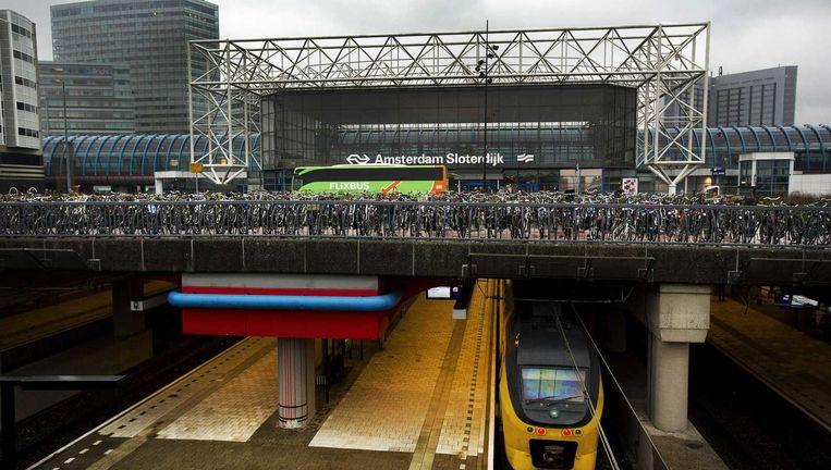 Een Flixbus bij het station Amsterdam-Slotervaart. FlixBus beweert het traject Eindhoven-Hengelo ruim een half uur sneller te kunnen afleggen dan de NS. Dat kost de busreiziger 9 euro. De NS rekent 22,93 euro, zonder korting. Beeld ANP