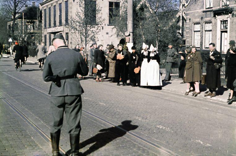 Duitse militairen vermengen zich tijdens de bezetting met Nederlandse burgers, van wie hier enkele in klederdracht, in Hillegom. De exacte datum van de foto is onbekend. Beeld Hollandse Hoogte / Alphons Hustinx