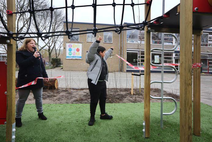Onder aanmoeding van directeur Mariska Snijder (l) knipte Amir Bittich (12) uit groep 8A het laatste lintje ter opening van het nieuwe schoolplein van basisschool John F. Kennedy in Breda door.