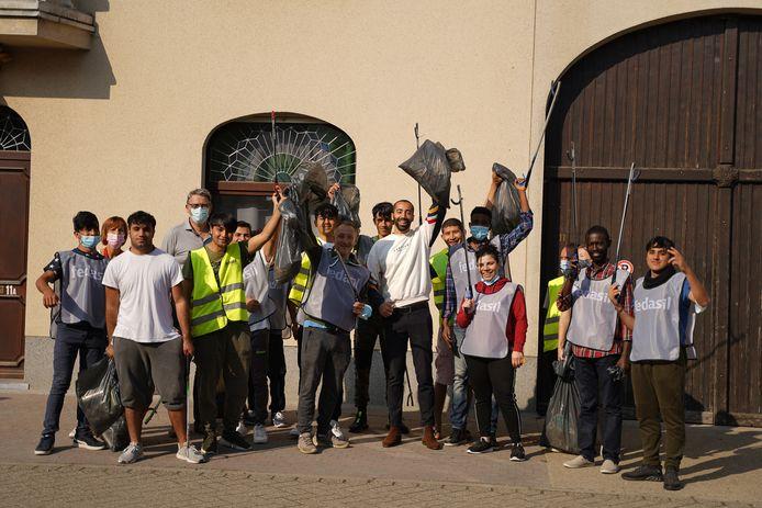 Staatssecretaris Sammy Mahdi, burgemeester Boudewijn Herbots en bewoners asielcentrum Zoutleeuw rapen zwerfvuil op World Cleanup Day.