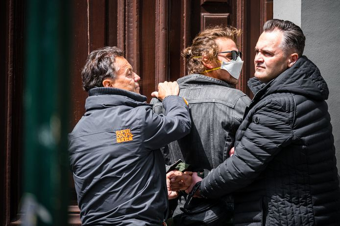 Jasper van den Elshout (met mondkapje) wordt door twee beveiligers van Forum voor Democratie in bedwang gehouden.