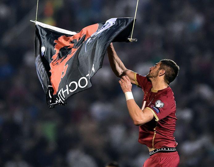 Servische verdediger Stefan Mitrovic probeert de vlag met nationale Albanese symbolen van de drone te trekken.