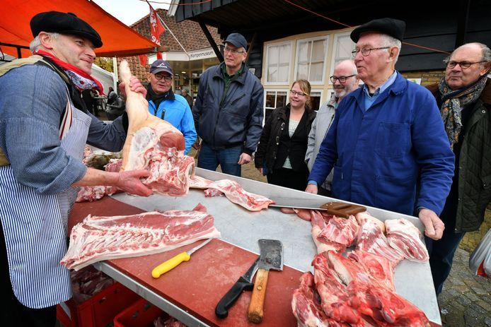 Jan Mekenkamp (tweede van rechts) als dé promotor van de jaarlijkse slachtvisite in Enter. Links, achter de tafel slager Vincent Roetgering.
