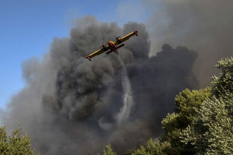Een blusvoertuig stort water uit boven een bosbrand bij Labiri, nabij de Griekse stad Patras. Beeld AFP