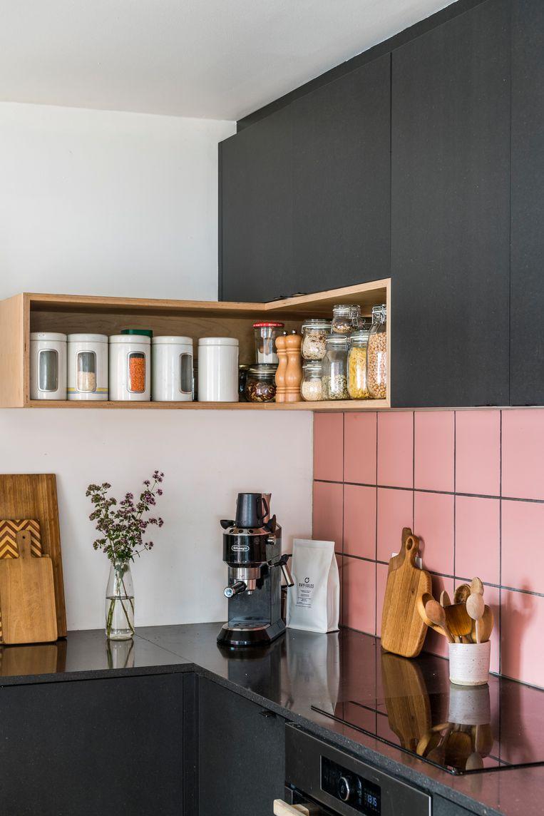 Voor het ontwerp van de keuken lieten Jeff en Hanne zich inspireren door de materialen die ze vonden. Het resultaat is een gedurfde combinatie van roze muurtegels en zwarte MDF-kasten Beeld Luc Roymans