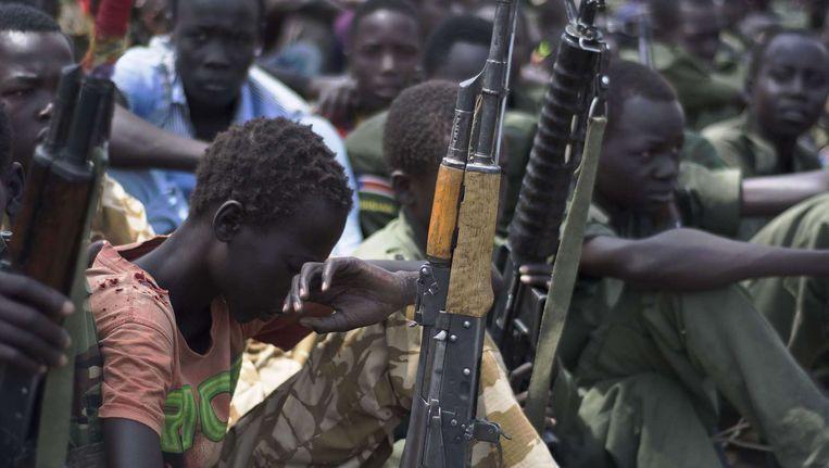Jonge jongens, kindsoldaten, zitten met hun geweren bij ontwapenings-, demobilisatie- en reïntergratieprogramma van UNICEF en partners in Pibor, Zuid-Soedan. Beeld null