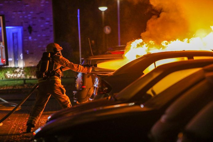 Een medewerker van de brandweer in Apeldoorn moet alle zeilen bijzetten om de autobrand onder controle te krijgen.