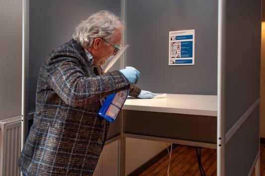 Jozef van der Maas, ook raadslid van HOI Werkt, poetst tussen het aantal stembuurten het hokje schoon.