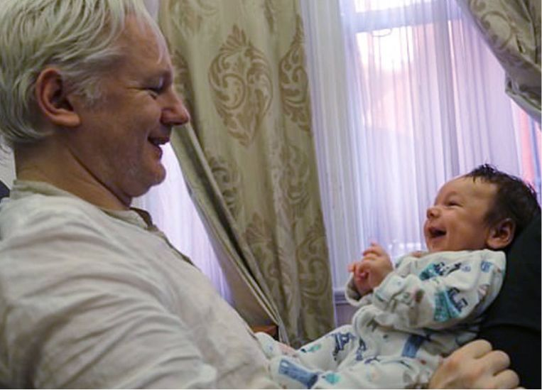Julian Assange met zijn zoontje Gabriel, toen hij nog in de ambassade verbleef. 'Hun papa is tegenwoordig niet meer dan een stem aan de telefoon, want nu hij in de gevangenis zit, mogen we niet videobellen met elkaar.' Beeld