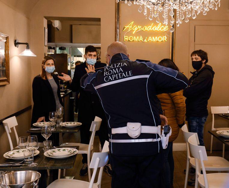 Een Italiaanse politieagent in gesprek met de eigenaren van restaurant Agrodolce in Rome. Het restaurant ging vorige week open, terwijl er een lockdown geldt voor de horeca. Beeld EPA