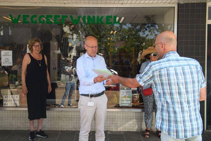 Vrijwilliger Hans Nijhof (r) en initiatiefnemer Carin Nijhuis (l) van de Weggeefwinkel overhandigen woensdagmiddag een petitie aan wethouder Bas van Wakeren. De winkel moet het pand verlaten en is op zoek naar een nieuwe locatie.