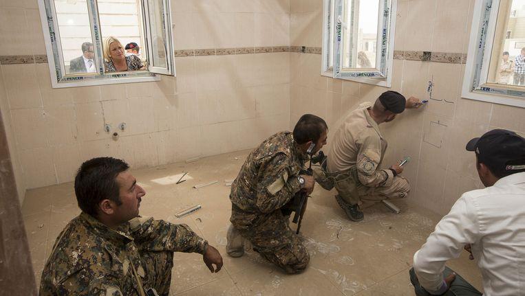 Minister Hennis kijkt hoe een Nederlandse militair Iraakse soldaten instrueert op een oefenterrein bij de Iraakse stad Erbil. Beeld Sjoerd Hilckmann
