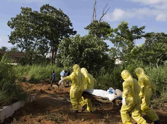 Hulpverleners dragen een ebolaslachtoffer naar een begraafplaats in Liberia.