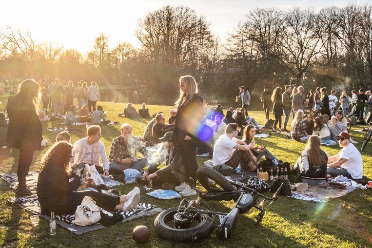 Jongeren komen toch bij elkaar in het Vondelpark op een mooie dag tijdens de lockdown in februari 2021.  Beeld Joris van Gennip