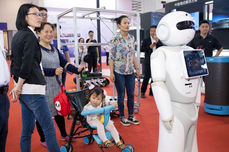 Bezoekers kijken naar een robotdemonstratie.  Beeld Ruben Lundgren