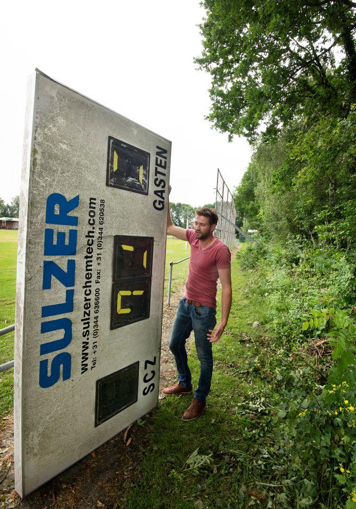 Voorzitter Jan-Justin Jansen met het scorebord wat vernield is door noodweer.