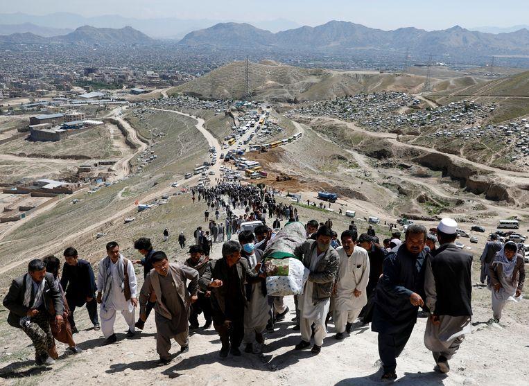 Mannen dragen de kist van een van de slachtoffers van een aanslag zaterdag op een middelbare school in Kabul.  Beeld REUTERS