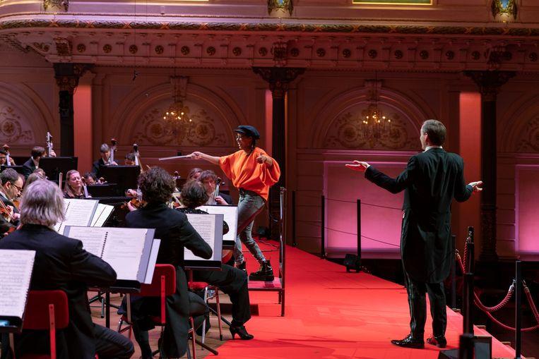 Eva Cleven dirigeert het Nederlands Philharmonisch Orkest. Dirigent Stijn Berkouwer kijkt toe.  Beeld Elmer van der Marel
