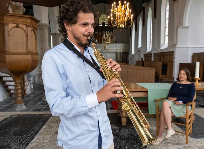 Holgerd Vachlis laat zijn saxofoon al even klinken in de Adriaanskerk, terwijl zijn partner Roslin Prager toehoort.