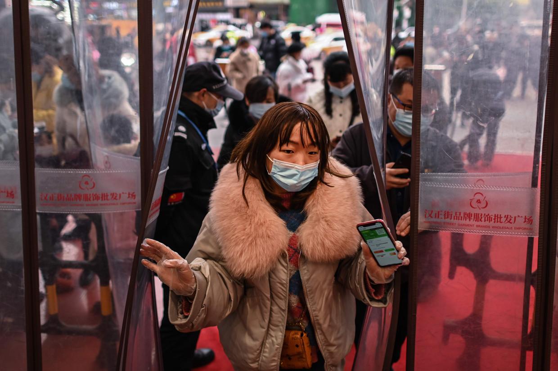 Een vrouw gaat een winkelcentrum in Wuhan binnen.