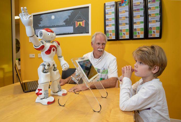 Robot Ziggi met Keano de Vos. Kinderarts Gert Jan van der Burg kijkt op de achtergrond toe.