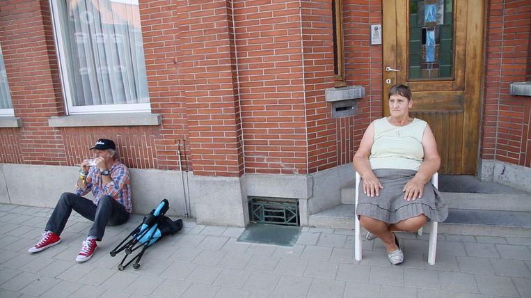 De oudere inwoners van Dranouter genieten van de stoet van festivalgangers die door hun dorp trekt. Beeld rv