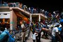 Aan een busstation in Delhi staat een lange rij van mensen die de stad proberen te ontvluchten