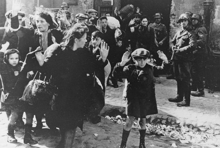 Joodse families worden door Duitse soldaten afgevoerd uit het getto van Warschau in april 1943. Beeld AP
