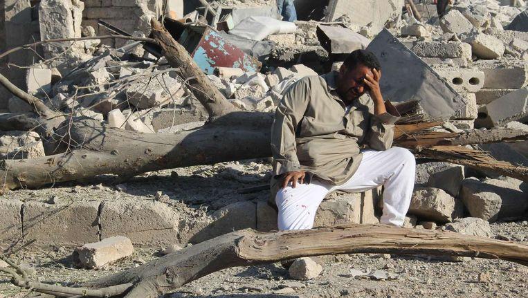 Een man treurt nabij zijn kapotgeschoten huis in Aleppo, op 11 augustus werd het gebombardeerd door het leger van Assad. Beeld AFP