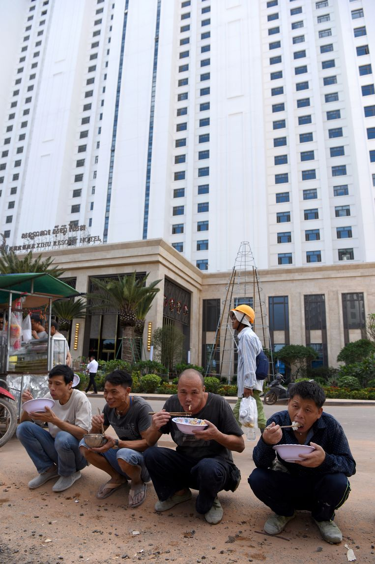 Chinese arbeiders eten hun lunch buiten op een van de straten van Sihanoukville. Beeld AFP