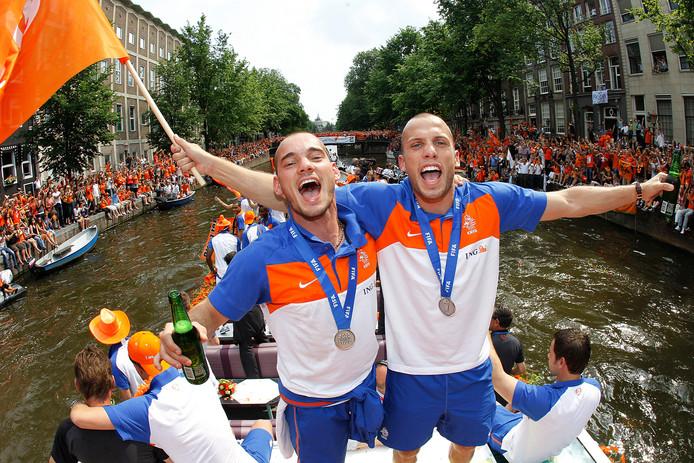 Wesley Sneijder en John Heitinga zwaaien naar het publiek tijdens de rondvaart van het Nederlands elftal door de grachten van Amsterdam.  Oranje kreeg na de verloren WK-finale in 2010 een huldiging in Amsterdam.