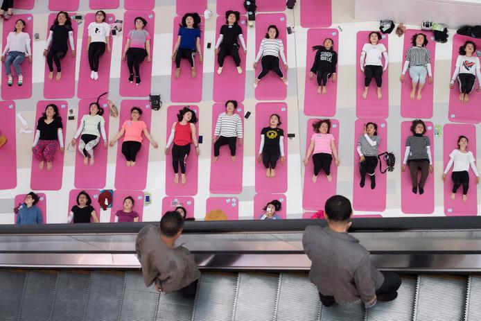 In het Chinese winkelcentrum in Taiyuan kijken voorbijgangers op een roltrap naar vrouwen die yoga oefeningen doen. Foto Stringer