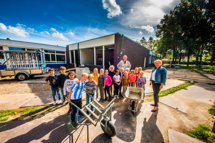 Directeur Hélène Lucassen (rechts) met leerlingen van groep 4A bij basisschool De Noorderborch die op dit moment verbouwd wordt.