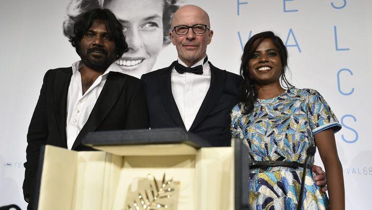 Regisseur Jacques Audiard (midden) op de foto met actrice Kalieaswari Srinivasan (rechts) en acteur Jesuthasan Antonythasan (links) na het winnen van de prestigieuze Gouden Palm. Beeld EPA/Franck Robichon