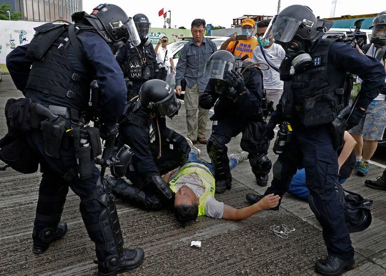 Een cameraman ligt gewond op de grond na een traangasaanval woensdag van de oproerpolitie.  Beeld AP
