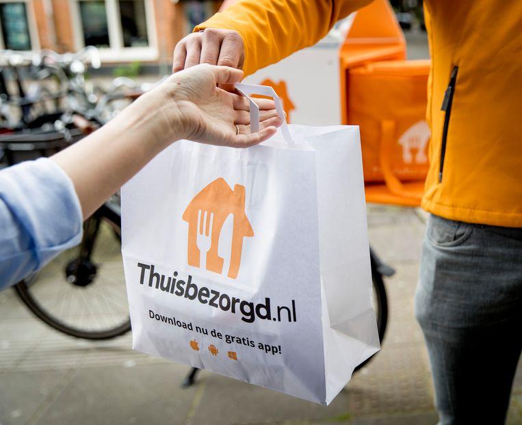 Een bezorger van Thuisbezorgd.nl verwerkt een bestelling. Beeld ANP XTRA