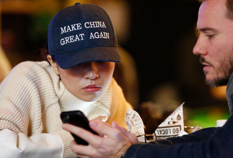 Een Chinese vrouw met een pet met Trump-achtige slogan in Peking Beeld epa