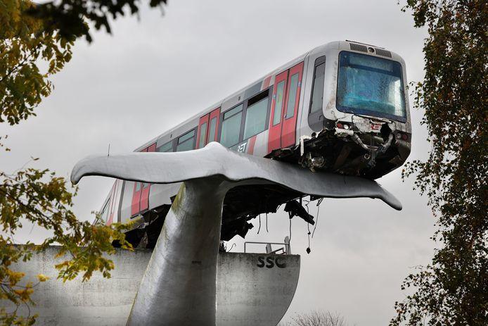 Het metrostel balanceert op een metershoge walvisstaart na de crash door het stootblok.