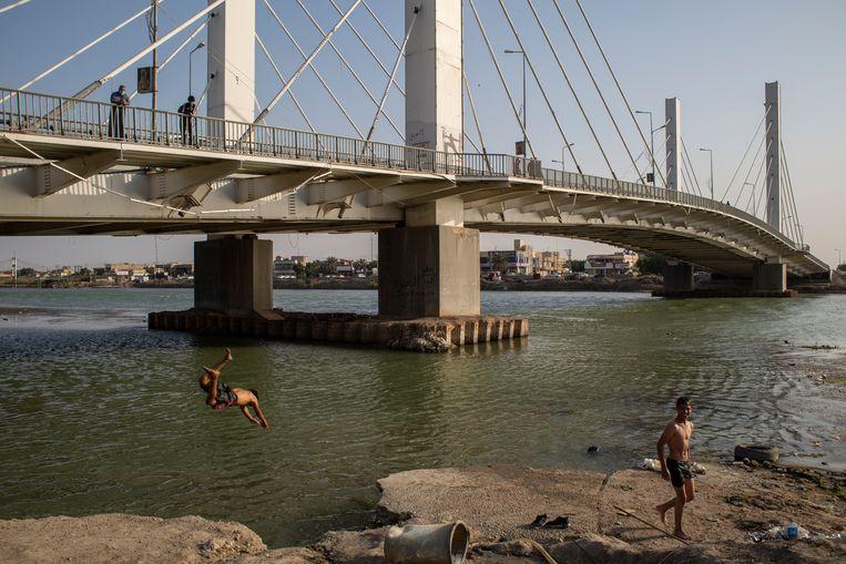 Jongeren zwemmen bij een brug in de stad Nasiriya. Beeld Hawre Khalid