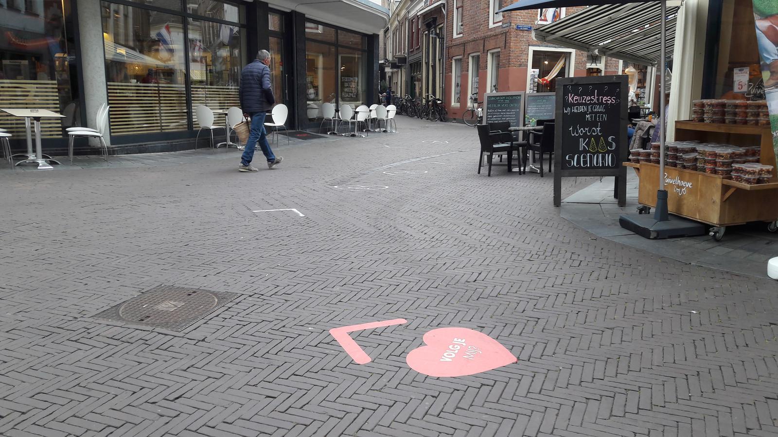 De harten- en pijlenstickers die de looprichting in het centrum aangeven, zijn alleen aangebracht op belangrijke punten. Zoals hier bij de kruising Beukerstraat-Korte Beukerstraat.