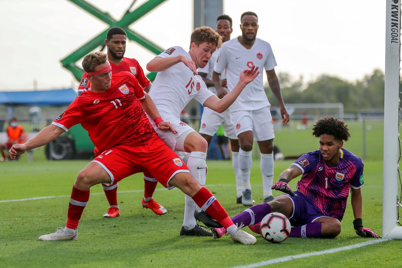 Frank Sturing - in het wit, nummer 15 - maakt het de verdedigers en keeper van de Cayman Eilanden lastig.