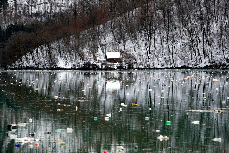 Plastic flesjes drijven in het meer. Beeld Darko Vojinovic / AP