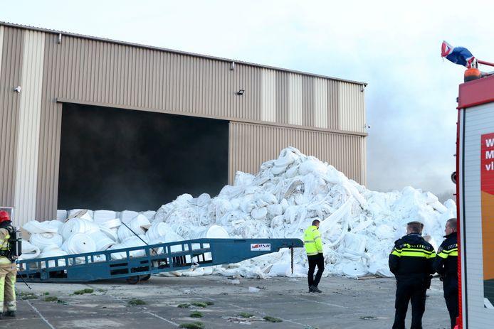 Brandweer en politie voor de loods van Recyclebedrijf Sortas op Urk waar de brand uitbrak.