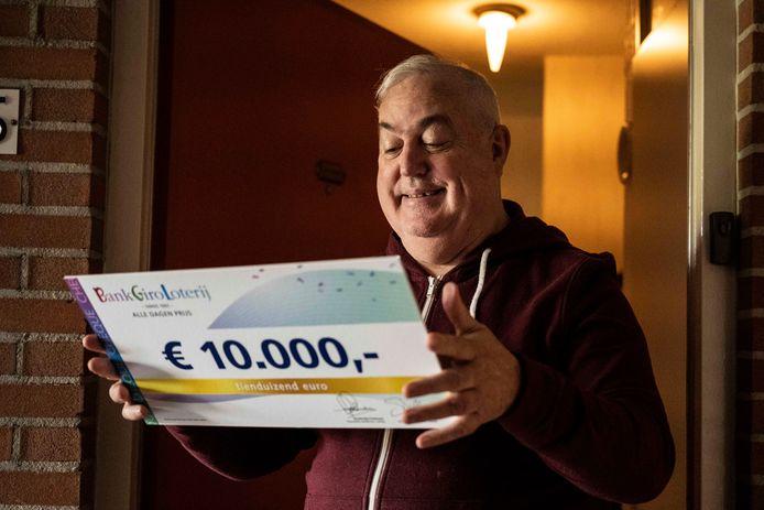 John met de cheque van tienduizend euro in zijn handen.
