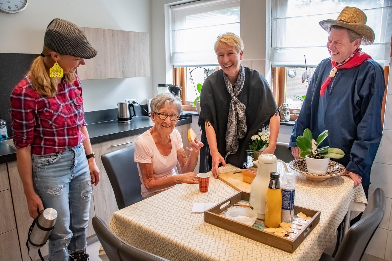 Toos van Rijthoven geniet van haar bakje koffie met een plakje cake, gefalnkeerd door Moniek Rooijakkers, Angelie Hesselmans en Cees de wit.