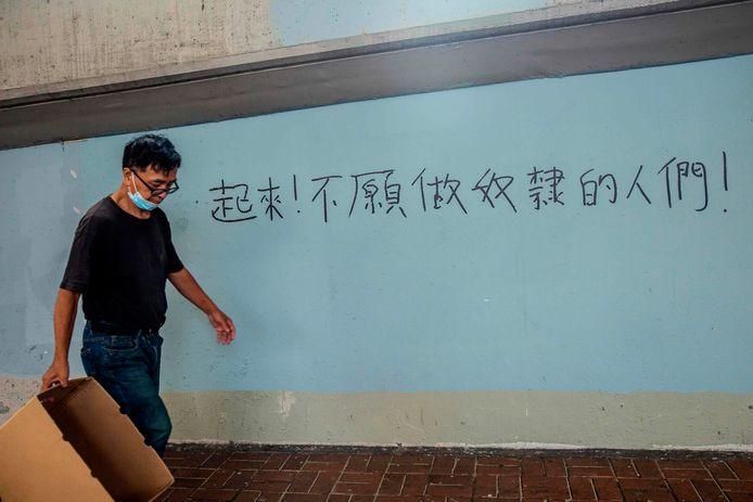 Een man in Hongkong loopt langs de leuze  'Sta op, gij die weigert slaaf te zijn!' Activisten gebruiken deze regel van het volkslied van China nu als protest tegen de overheid.