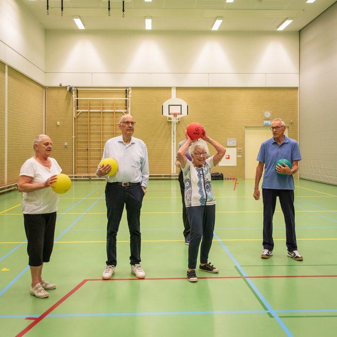 Mies legt aan voor een worp richting de basket, Piet (gele bal) kijkt toe.