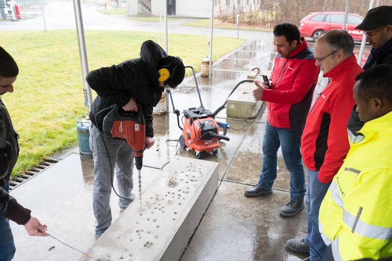 De bouwvakkers leren hoe ze stofvrij kunnen boren.