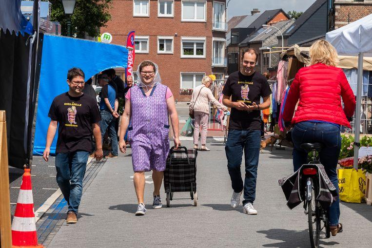 Schepen Bart Lambrecht moet verkleed als oud vrouwtje over de markt lopen. Zijn vrienden Willem en Geoffrey genieten met volle teugen.