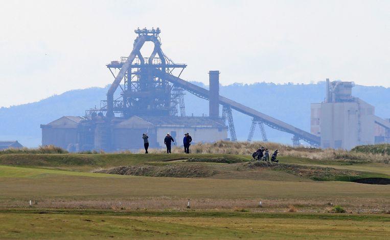 Mensen spelen golf in de buurt van de Tata Steel-fabriek in Hartlepool in Noordoost-Engeland op 3 mei 2021. Beeld AFP